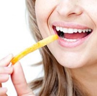 Close-up of a smiling woman eating fries isolated on a white background