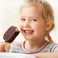 Child eating ice cream. Little girl at home