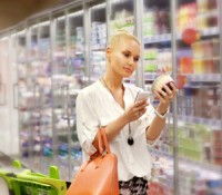 Woman shopping in supermarket reading product information. Check