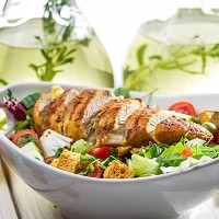 Fresh salad made of chicken, tomato, olive and fresh herbs