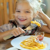 Beautiful laughing little girl sitting at table and eating French fries from your plate.