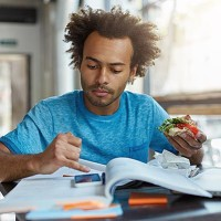 Indoor shot of black man with bushy hair looking in his smart phone eatting delicious sandwich resting after preparation for classes. Busy dark-skinned student eatting fast food messaging with friends