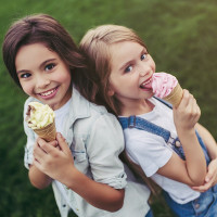 Little pretty girls having fun outdoor. Standing on green grass with ice cream in hands.